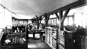 A look at the composing room in the early 20th century. Lead type in typecases dominate the picture.