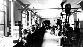 Workshop operations in the bindery with large transmission belts and shaft, around 1906
