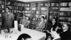 In October 1953, Sales Director Rudolf Wendorff (standing) presents the first volume in the Big Bertelsmann Lexikon (Encyclopedia)