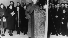 An emblematic picture - Reinhard Mohn, still in his soldier's cloak, speaks to his employees at the topping-out ceremony in 1947